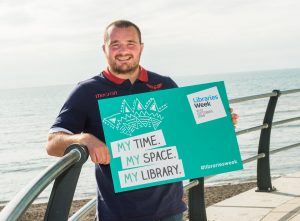 Man carrying Libraries Week promotional poster