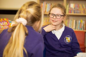 Two school pupils having a discussion on a library visit