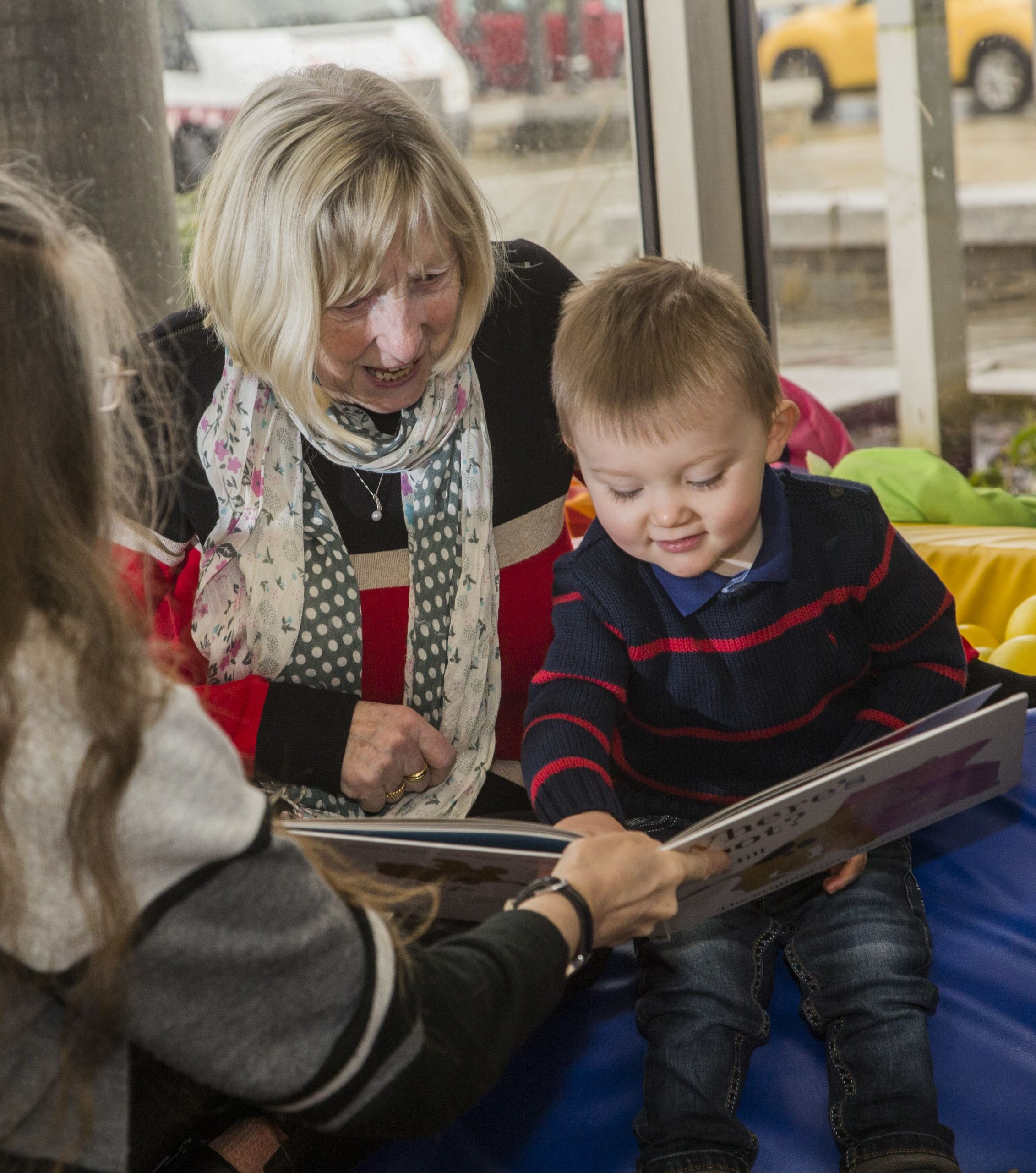 Adult and younger child reading picture books at Aberdare Library