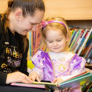 Mother and Child reading picture books at Children's Library Flintshire Libraries