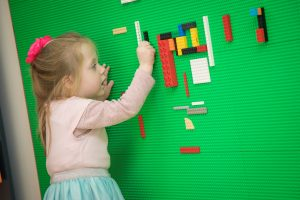 Young child playing with lego at Awen Libraries