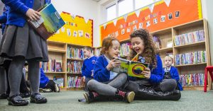 Two girls reading library books during a Class visit from local school at Maesteg Library Bridgend