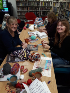 Group of people at Prestatyn Library Craft and Chat Group meeting up to learn how to crochet