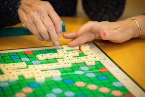 Two hand on a Scrabble board