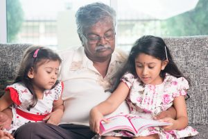 Two children reading books with an adult